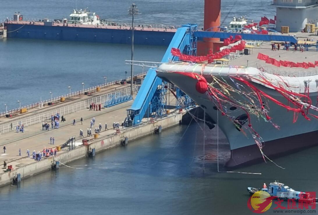 4月26日11:30,岸上工人在拖拽航母上的纜繩,靠泊仍在繼續(大公文匯全媒體記者宋偉攝)