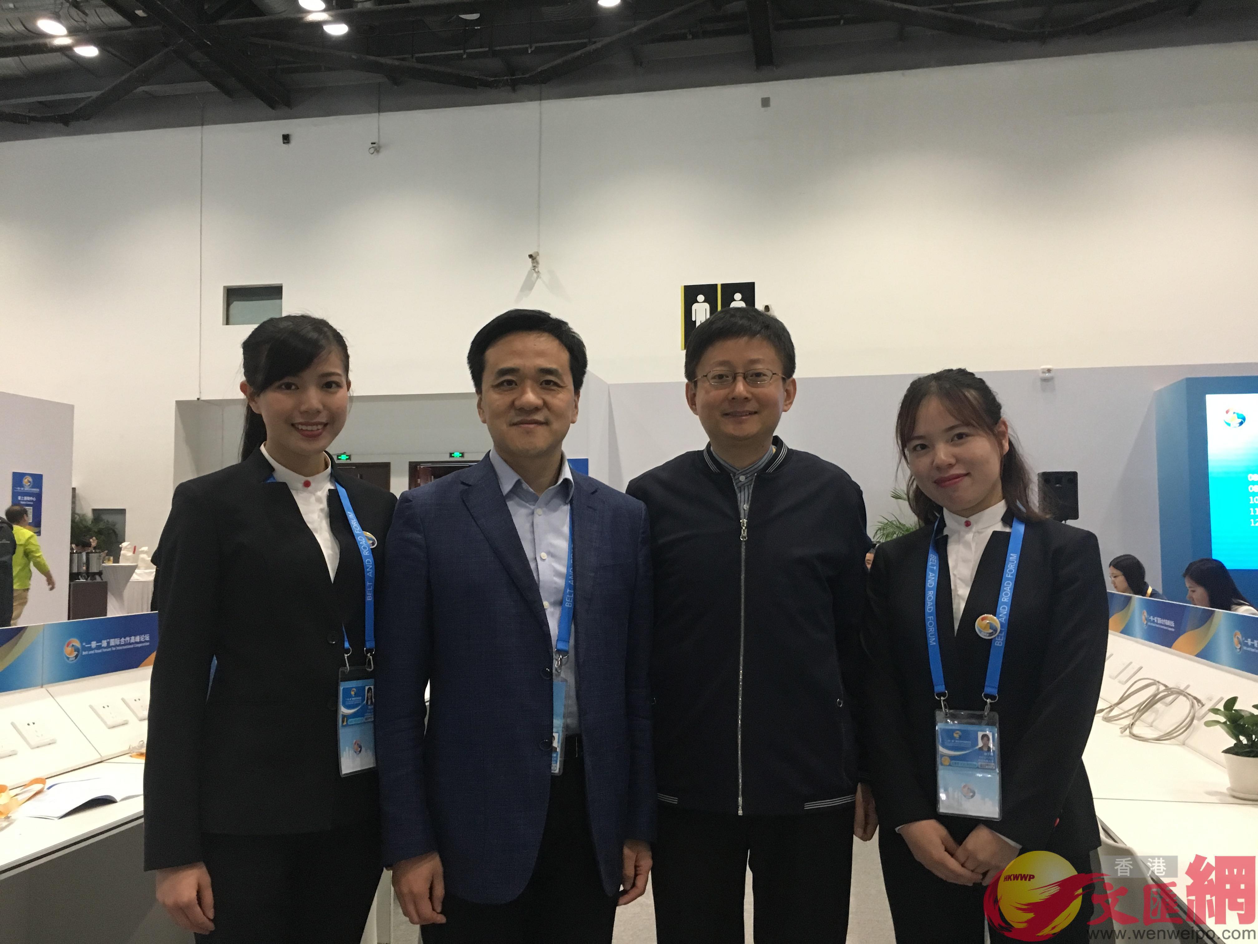 清華大學、中國傳媒大學、中國人民大學志願者在峰會新聞中心現場,左二為媒體公共工作區負責人張冬林。