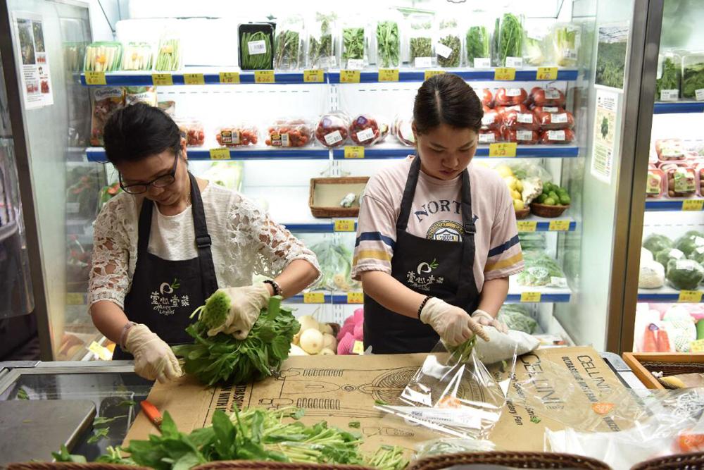 在香港正街的一家蔬菜店,工作人員在包裝莧菜