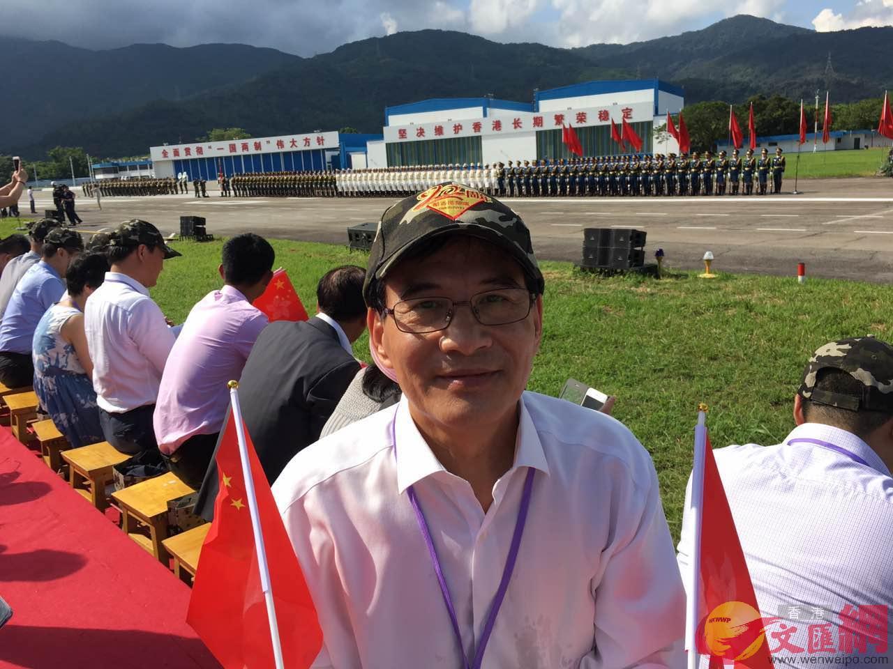 林際平手持國旗和港旗,在駐港部隊三軍儀仗隊前觀禮(林際平提供)
