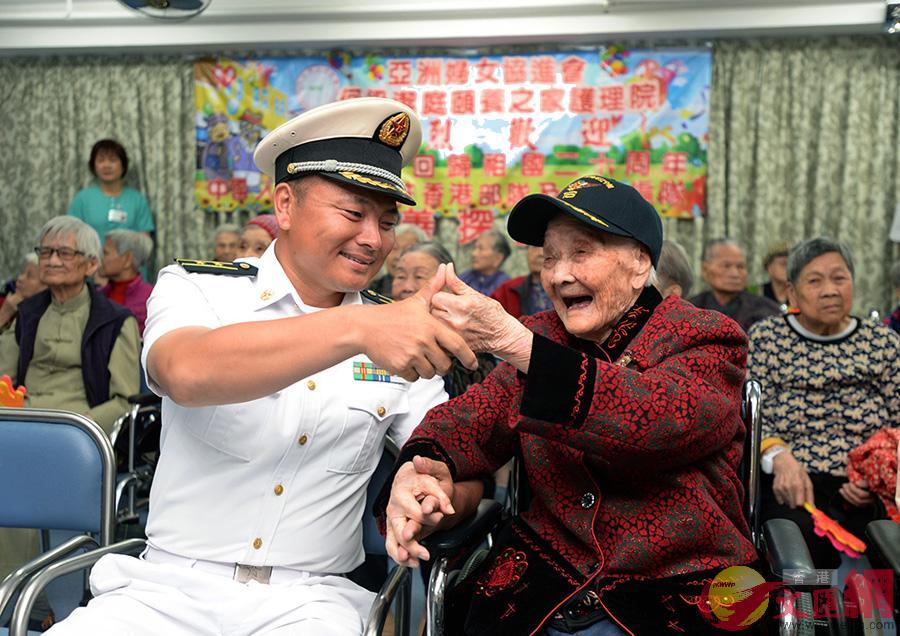 銀川艦副政委趙金路中校與110歲長者謝婆婆對碰拇指,相互祝福鼓勵(大公報記者林良堅攝)