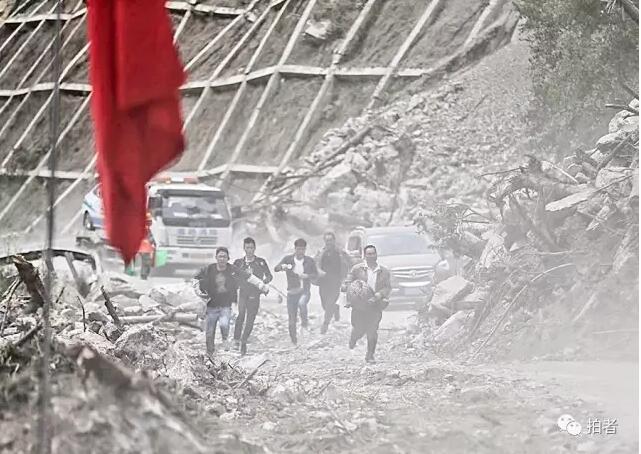 8月10日,九寨溝景區S301省道,武警交通正在指揮單向放行,通過坍塌嚴重的危險路段時,很多人快速跑步前行。