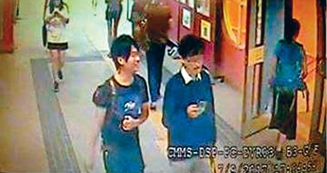 兩名涉事者年約二十歲,其中一人戴眼鏡,穿白恤衫、深色毛衣及淺色長褲;另一人穿深色T恤及長褲,面露笑容。(圖源:香港頭條日報)