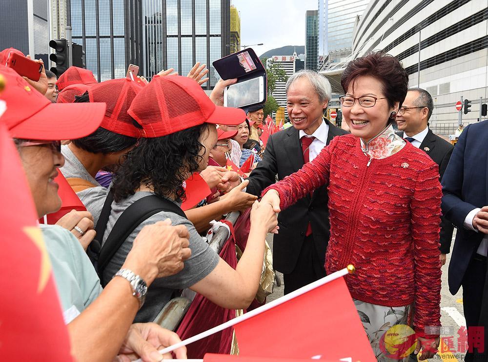 林鄭月娥及丈夫林兆波博士出席升旗儀式前與市民握手