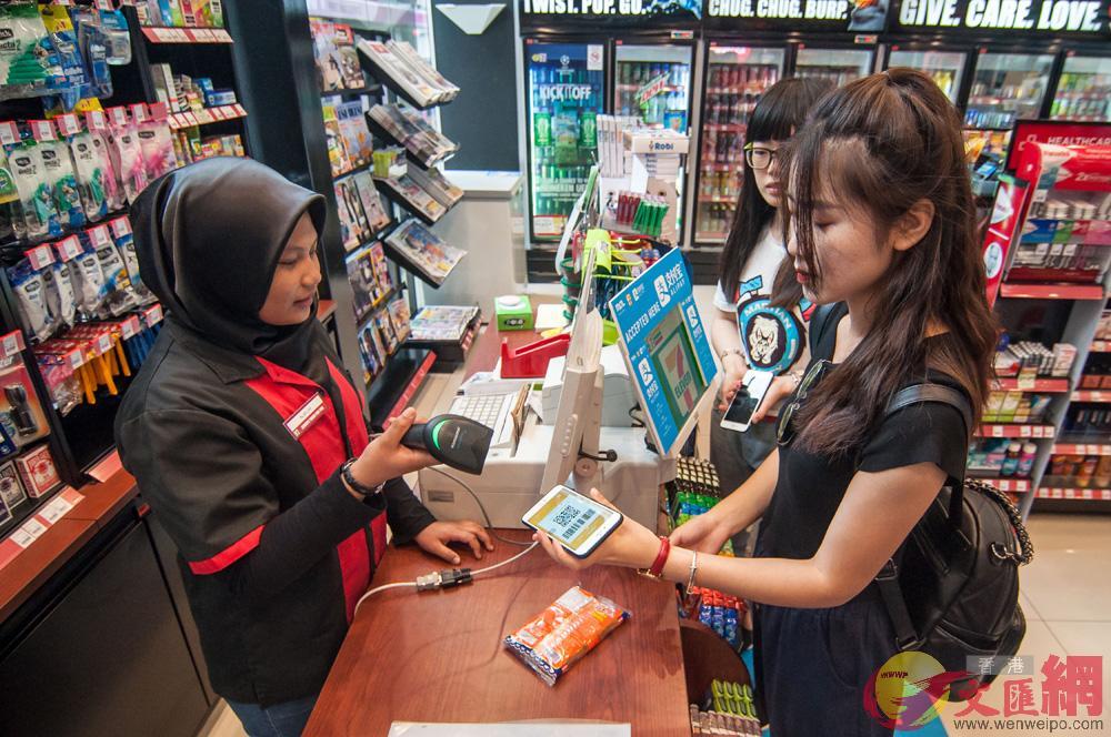 在馬來西亞吉隆坡,人們在便利店使用支付寶服務\資料圖片