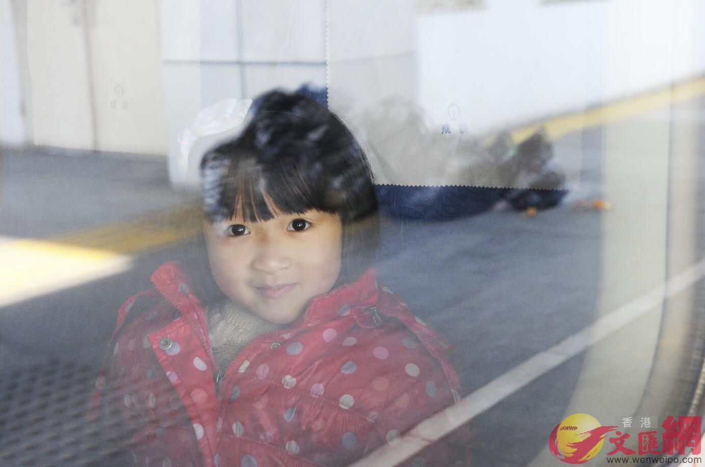2016年1月24日,成都火車站開出的春運高鐵上,一名小旅客露出笑容。