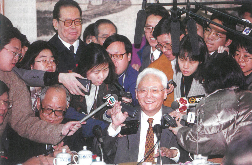1995年3月7日,魯平到人大廣東代表團駐地,向港澳代表介紹預委會工作時,被眾記者圍困當中(中新社)