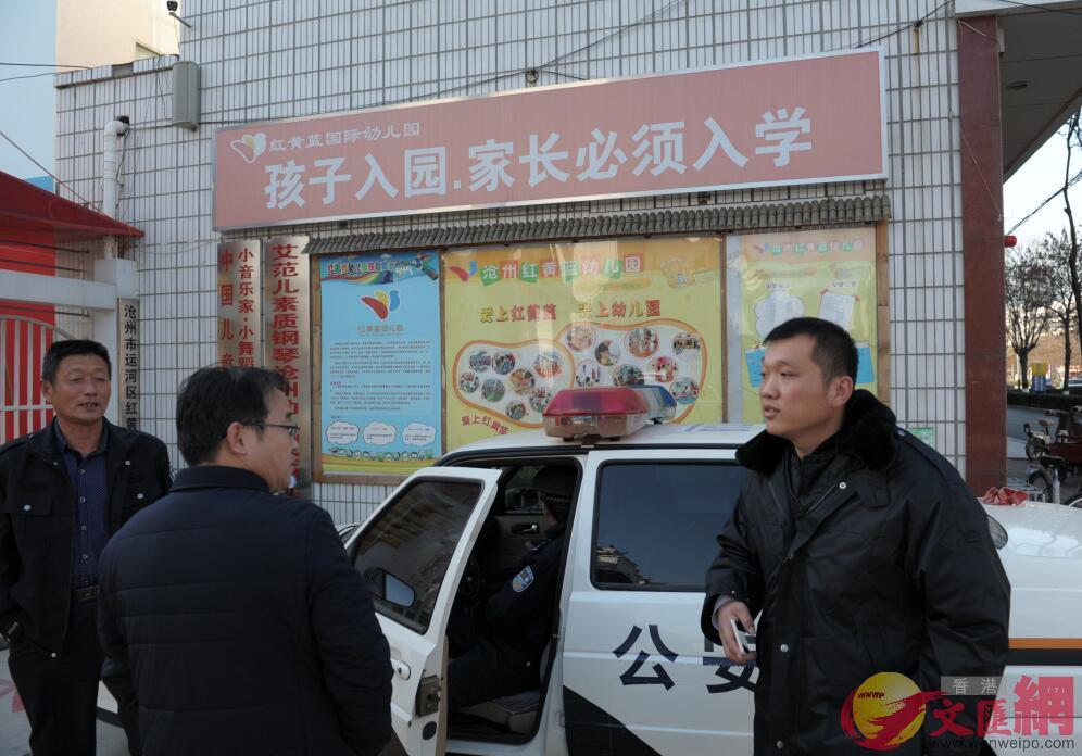 停業整改的滄州紅黃藍幼兒園大門口,仍有警察值班維持秩序,圖為執勤警察盤查圍觀者身份(記者 顧大鵬 攝)