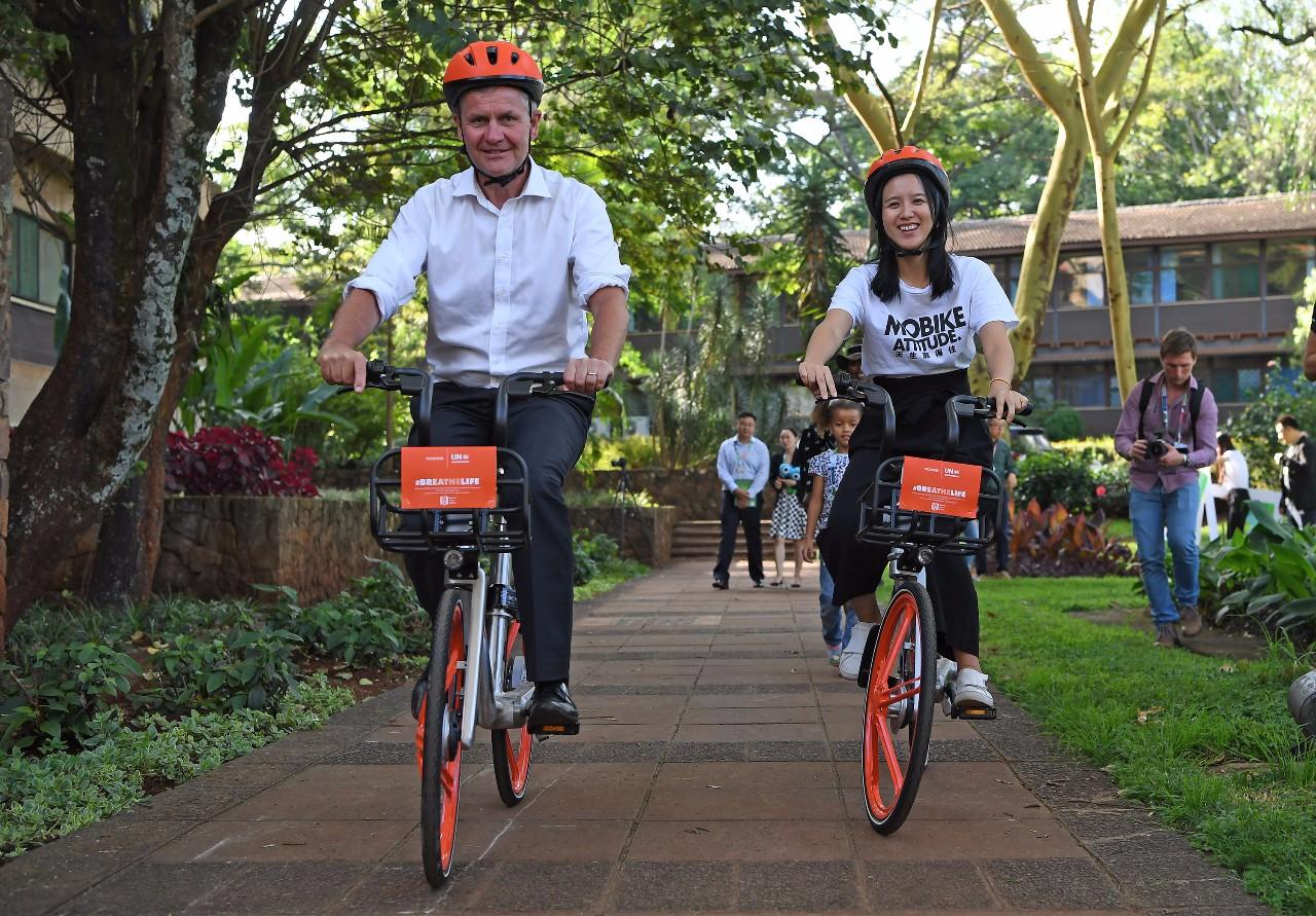 12月3日,在肯尼亞首都內羅畢,摩拜單車創始人胡瑋煒(右)與聯合國環境規劃署執行主任埃裡克·索爾海姆騎車同行。