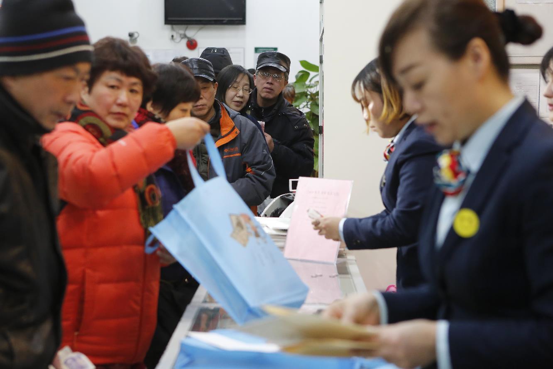 在上海浦東南路5000號中國郵政世博郵政支局營業廳內,民眾冒雨通宵排隊購買狗年特種郵票