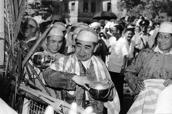 1960年4月,周恩來訪問緬甸時,身著緬甸民族服裝,手持銀碗,同緬甸人民歡慶潑水節。