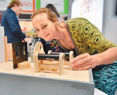 一名參觀者在玩具展現場試玩光學實驗遊戲盒。王 璽攝(新華社發)