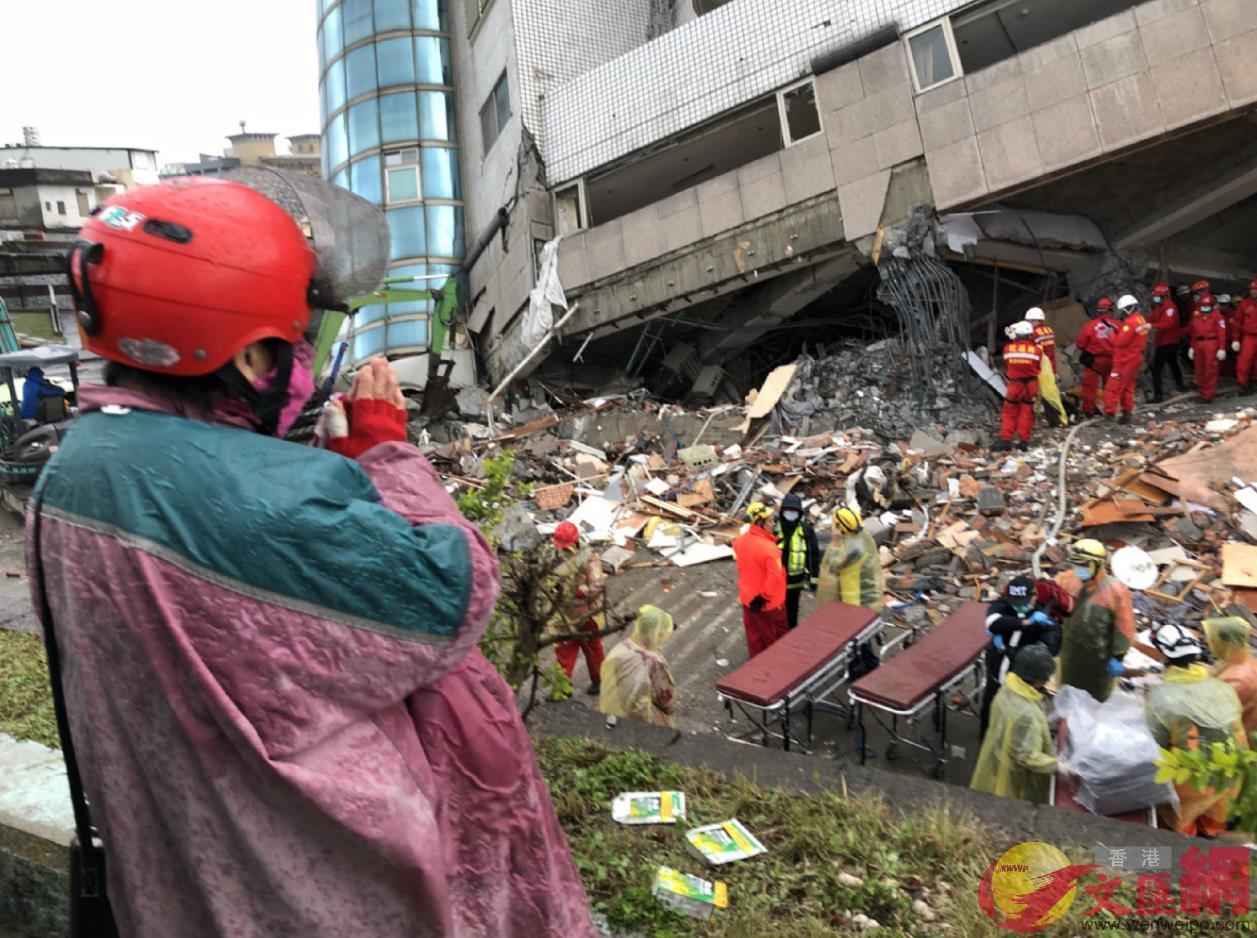 有民眾在倒塌的建物旁,合十為罹難者誦經(台灣「中央社」)