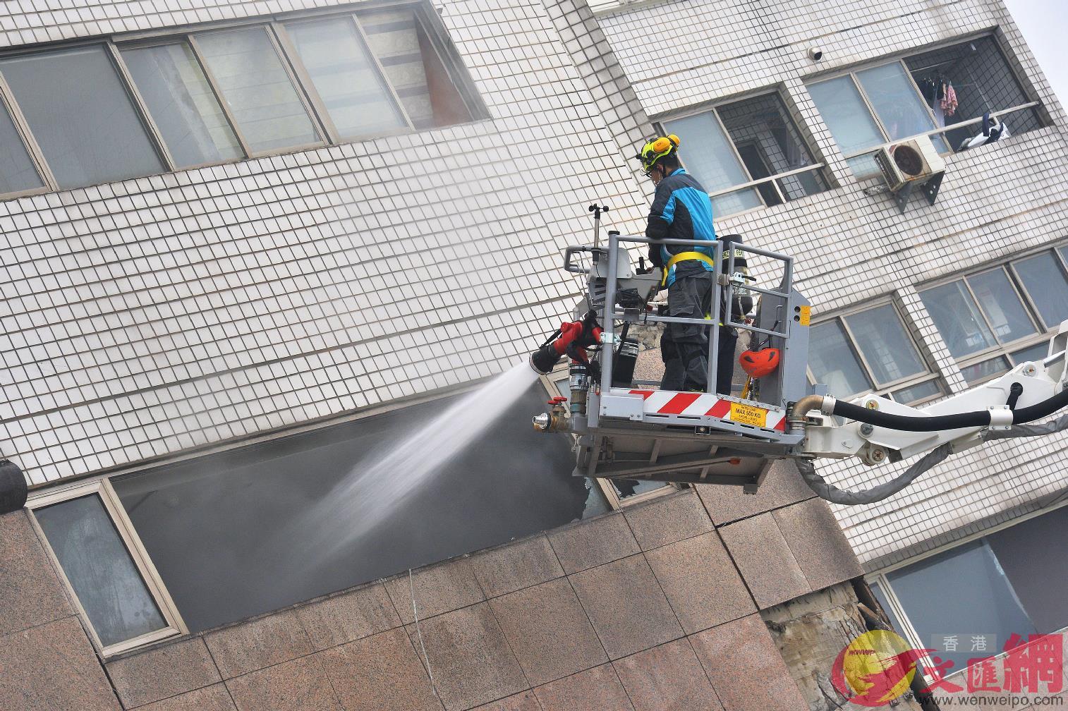 7日09:50:嚴重傾斜的雲門翠堤大樓內部起火悶燒,消防人員持續灑水。