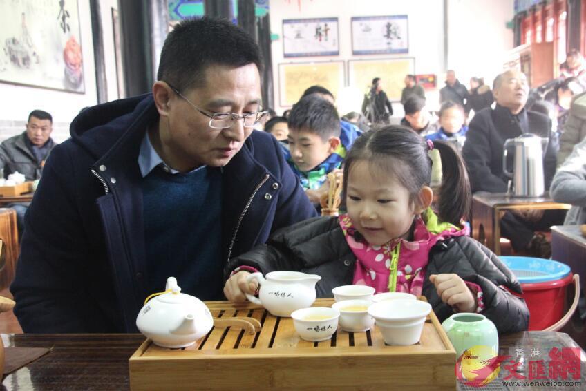 一位小女孩正在和爸爸學習傳統茶藝。