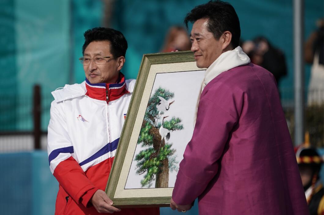 朝鮮代表團團長、體育省副相元吉宇(左)向江陵奧運村村長金琪勛贈送禮物