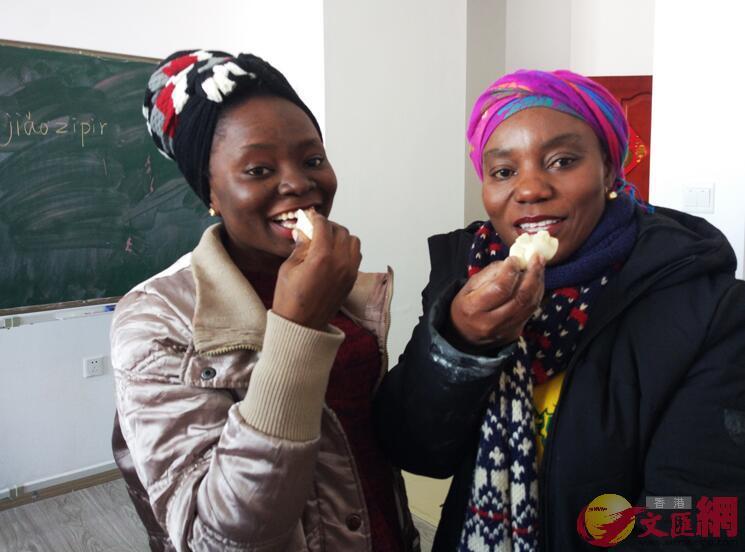 來自加納的「姐妹花」伊薩貝爾(左)和艾薇(右)對小巧玲瓏的餃子十分喜愛(記者 吳千 攝)