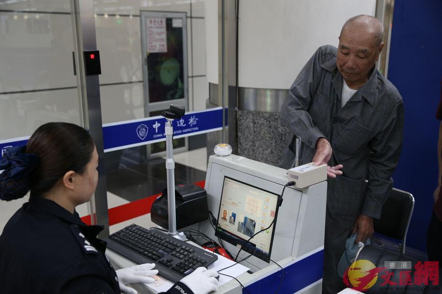 邊檢民警在臨時自助通關信息採集點為旅客採集信息