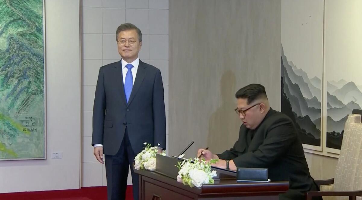 金正恩在「和平之家」一樓的留言簿上簽名(電視截圖)