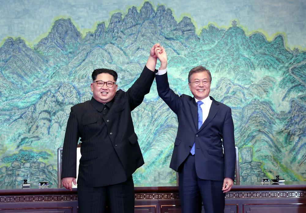 朝鮮最高領導人金正恩與韓國總統文在寅攜手高舉,同賀簽署《板門店宣言》。法新社