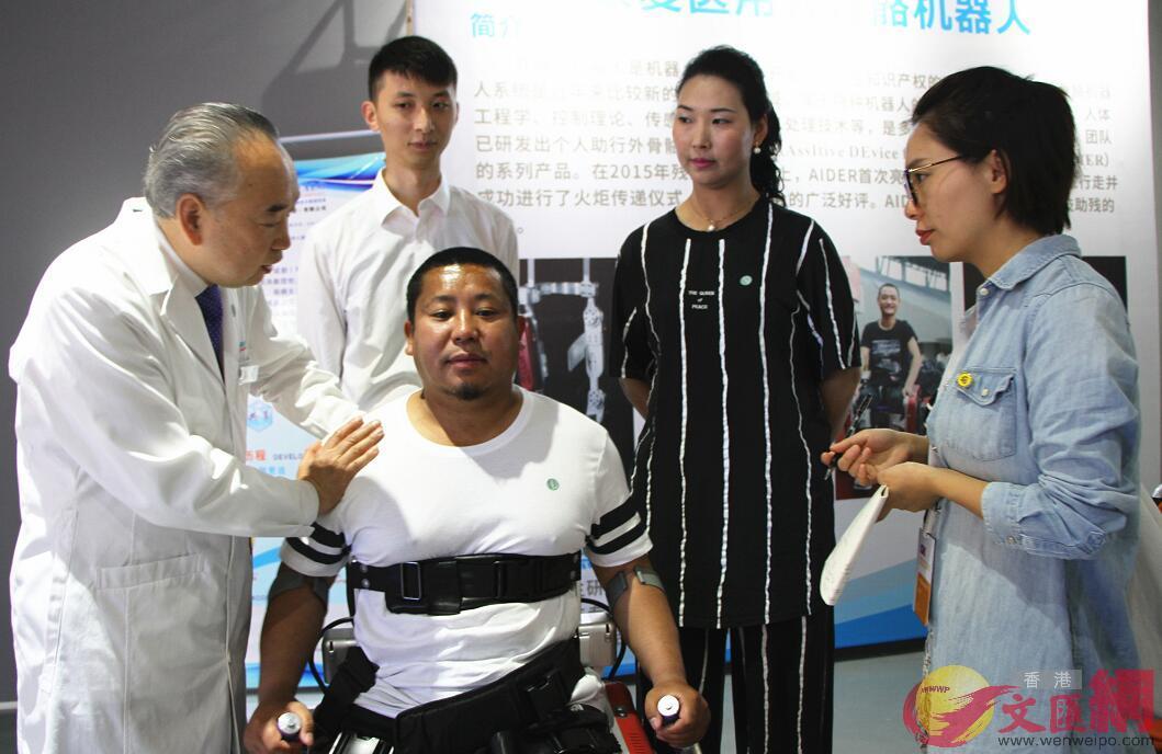 電子科大機器人研究中心醫學首席專家張安仁現場指導馬志傑運用外骨骼機器人系統。(記者 李兵 攝)