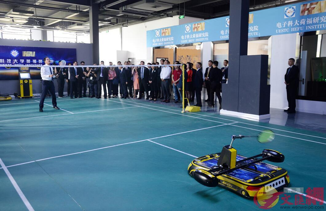 特區政府發展局局長黃偉綸與羽毛球機器人對陣。(記者 林良堅 攝)