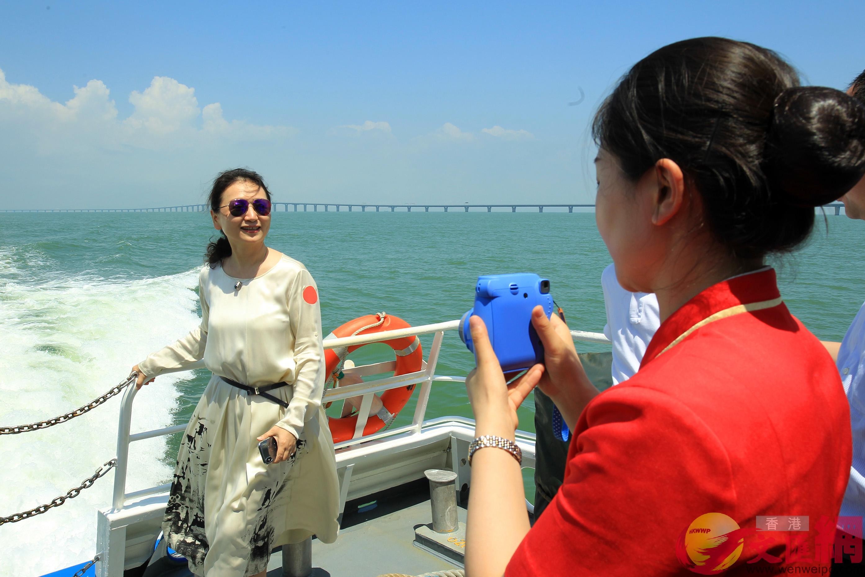 游客乘坐内地最快的新型豪华双体客船游览,纷纷以大桥为背景拍照留念。(記者 方俊明 摄)