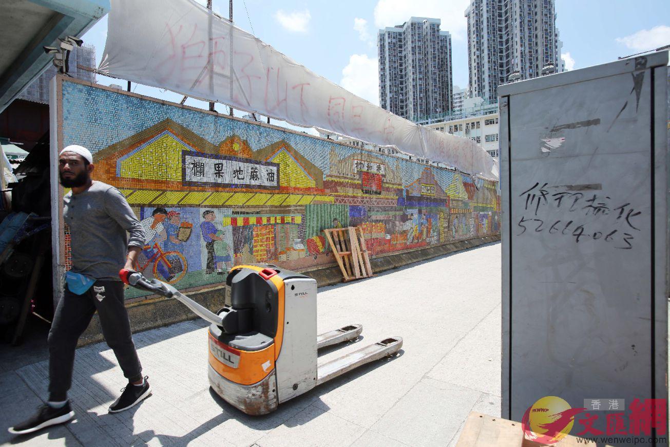 工人搬運貨物後經過面向渡船街外圍的壁畫