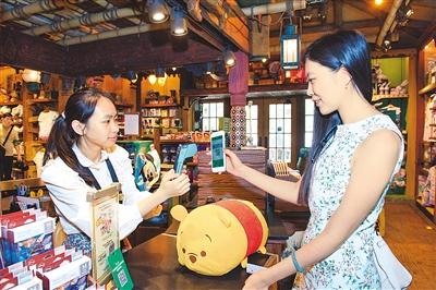 遊客在香港迪士尼樂園體驗用微信支付購買紀念品。