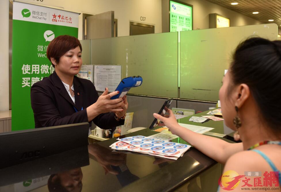 內地遊客在香港國際機場港中旅巴士售票處用微信支付購買前往廣東的巴士車票。
