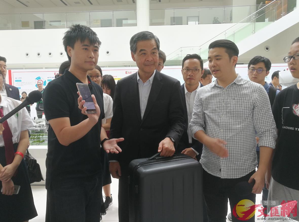 全國政協副主席梁振英在前海夢工場體驗隨身寶的一款智能行李箱(記者 黃仰鵬 攝)