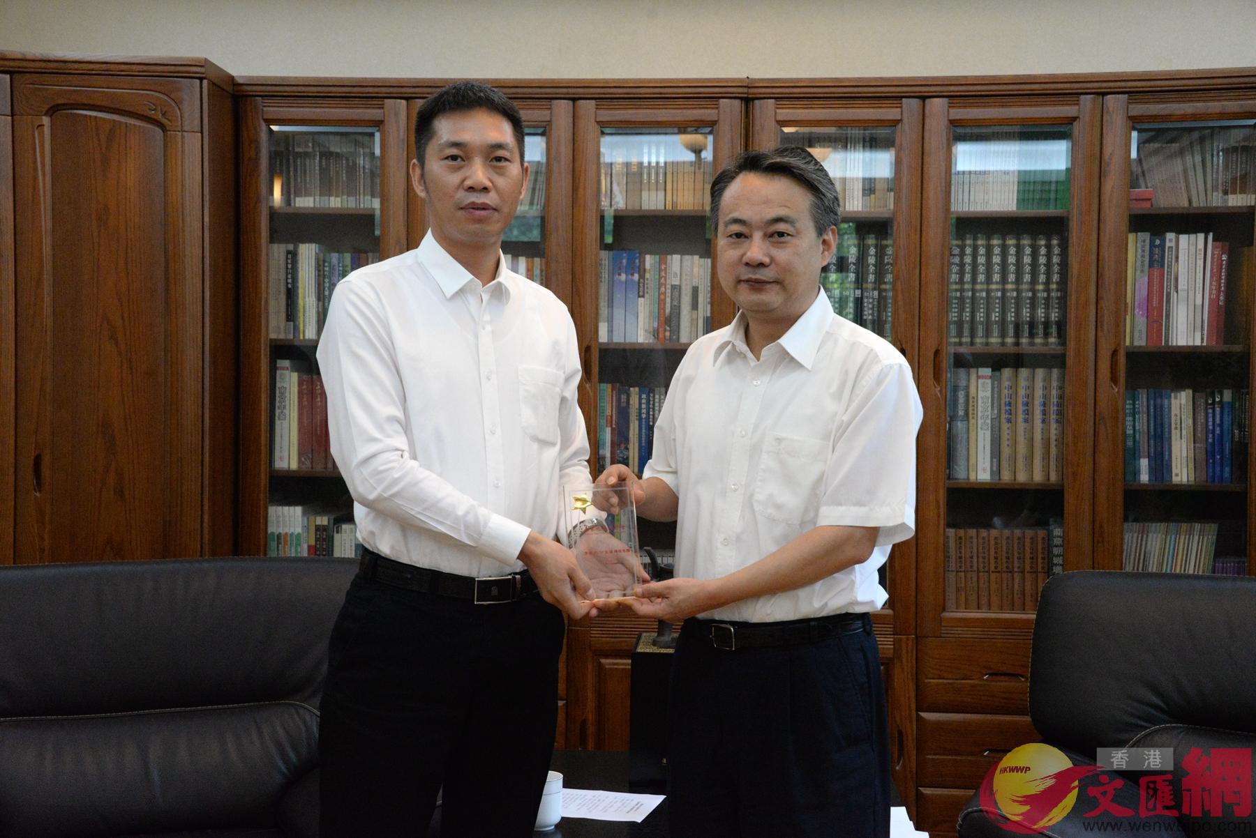 「未來之星」同學會副主席、香港大公文匯傳媒集團華東新聞中心主任楊明奇(左)向陳勇贈送紀念品。(記者賀鵬飛 攝)