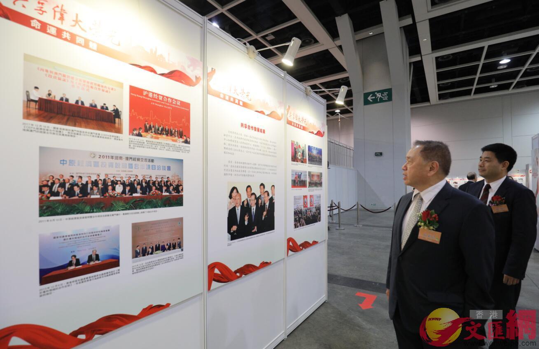 全國政協常委、香港僑界社團聯會會長余國春(左)觀看圖片展(全媒體記者麥鈞傑攝)