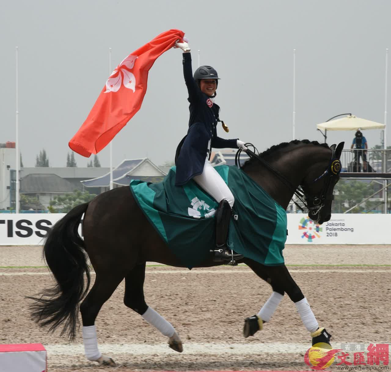 蕭頴瑩手持區旗與她的夥伴一同揚奔慶祝