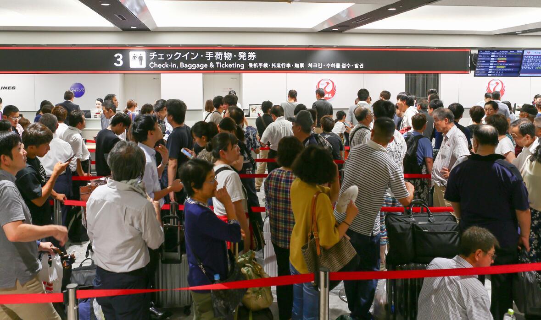日本北海道新千歲機場國內航線航站樓內,旅客排隊辦理值機手續。新千歲機場7日部分國內航線重啟,仍有大量原定航班被取消。