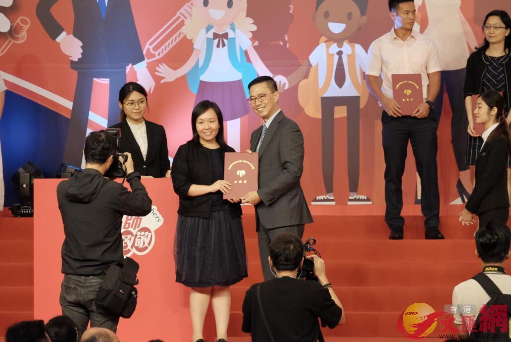 教育局局長楊潤雄(右)為優秀教師頒獎