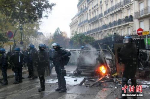 當地時間12月1日,巴黎再次發生大規模示威活動。示威者聚集在凱旋門。大批防暴警察尋求控制巴黎示威造成的混亂局面。圖為防暴警察在巴黎市中心正在燃燒的車輛前嚴密警戒。中新社