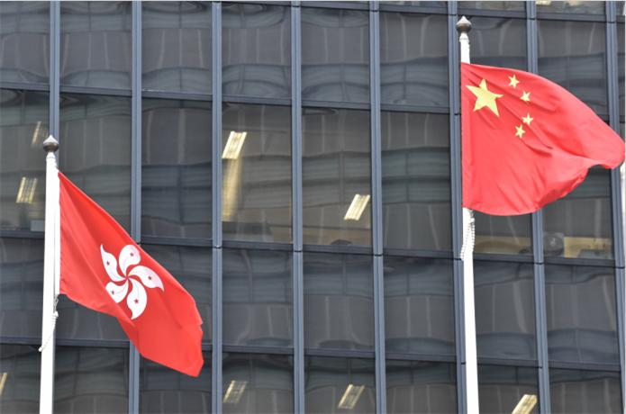圖為在政府總部外升起的國旗和區旗(中新社)