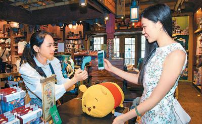 圖為遊客在香港迪士尼樂園體驗用微信支付購買紀念品。新華社