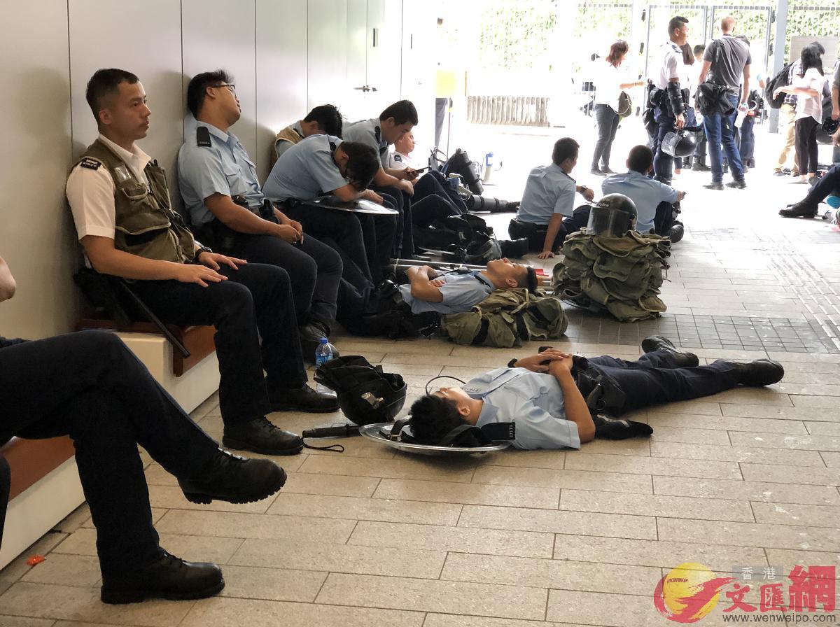 部分警員徹夜布防後疲憊不堪,坐在通道上休息。(全媒體記者陳旭健攝)