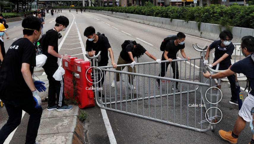 示威者們在灣仔用塑料束線帶來將路障、鐵馬以及道路指示標識捆綁固定起來。