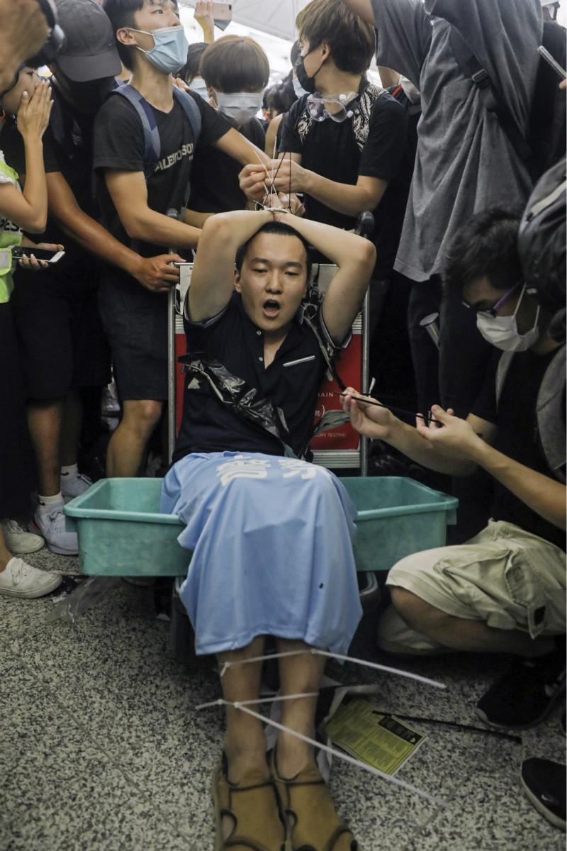 環球時報記者被綁在機場手推車上(美聯社)