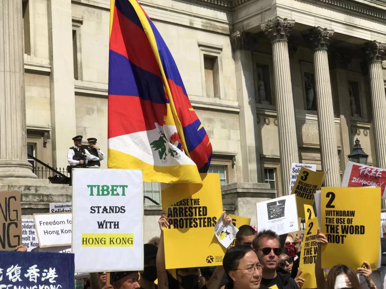 示威者人群中有人揮舞著象徵「藏獨」的雪山獅子旗