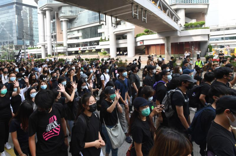 大批亂港分子戴上口罩蒙面,公然違法,並佔據一條行車線。圖片來源:大公報
