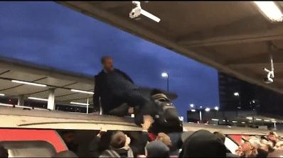 站在倫敦一列火車車頂的一名抗議人士被憤怒的上班族拉了下來。(英國《鏡報》)