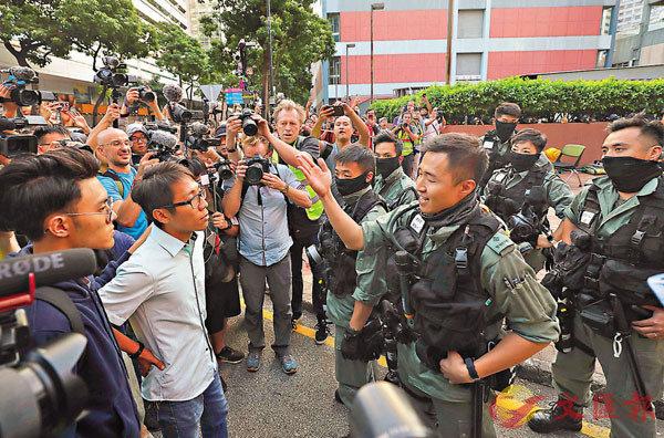 ■一班自稱公民黨新血的人,區選得勝後集結理大警察封鎖線外,試圖硬闖入理大不成功。 香港文匯報記者 攝
