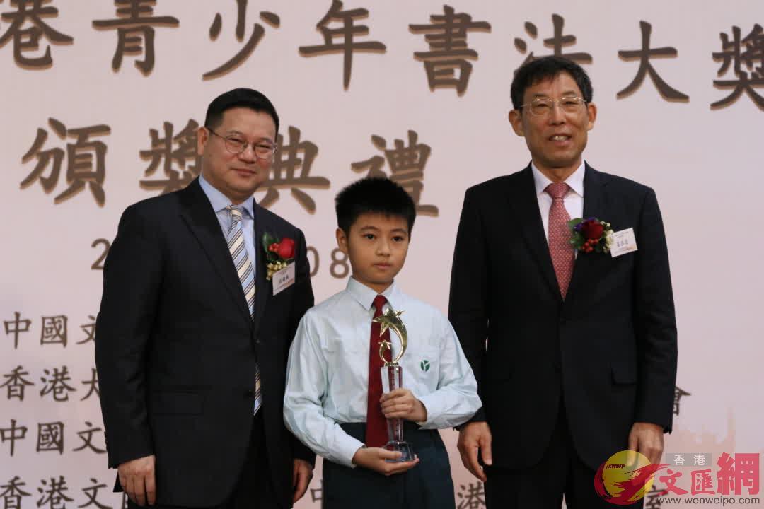 姜在忠(右)及香港中聯辦宣傳文體部副部長張國義(左)為毛筆組特等獎獲得者頒獎