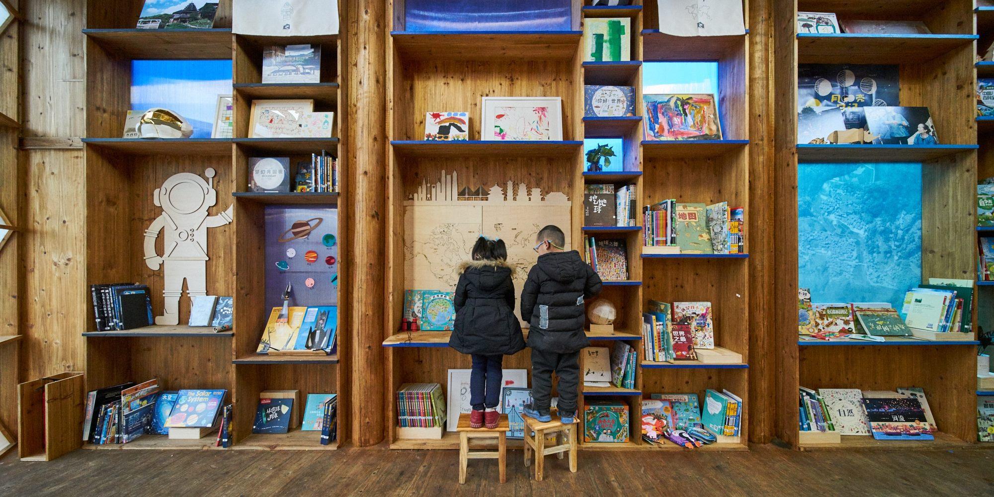 兒童在書架前遊玩。