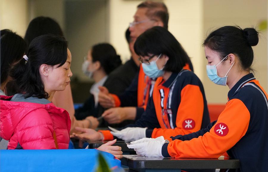 高鐵西九龍站的檢票員戴上口罩核查旅客身份信息。(香港中通社)