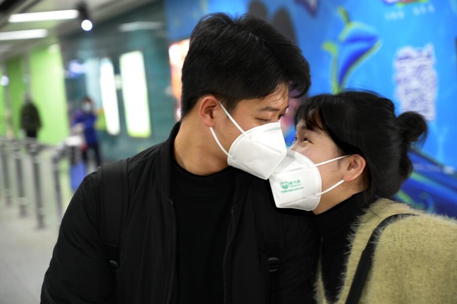 佩戴口罩的青年男女在廣州長隆地鐵站交流。(中新社)